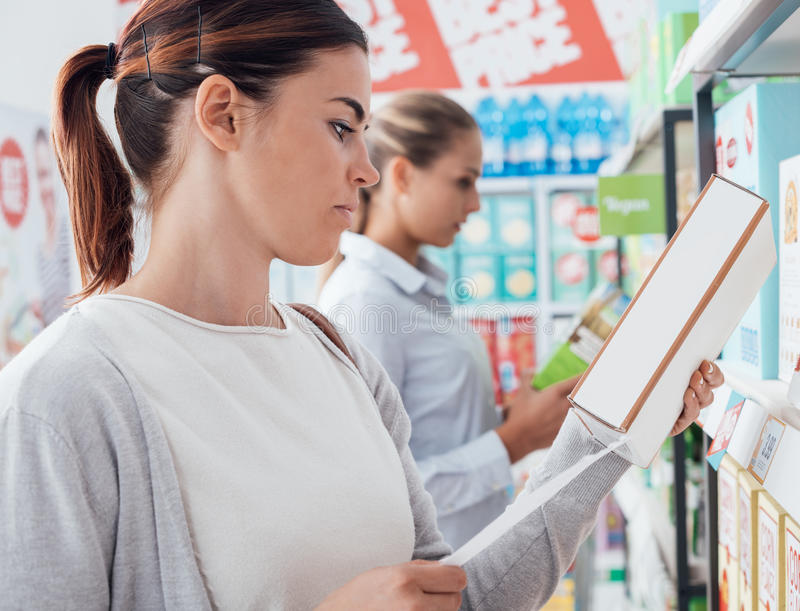 Women shopping at the supermarket. Woman shopping at the supermarket and reading nutrition facts and ingredients on a box royalty free stock photo