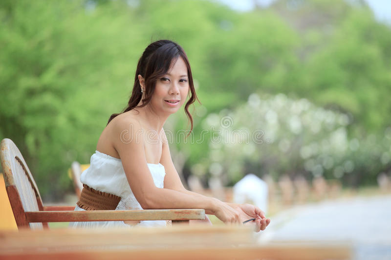 Women In Short Dress Sitting In The Park Royalty Free Stock Photo