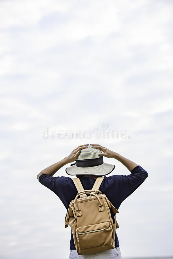 Women shoulder backpack and Wear a hat Background sky royalty free stock photography