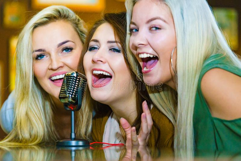 Women singing with microphone royalty free stock image