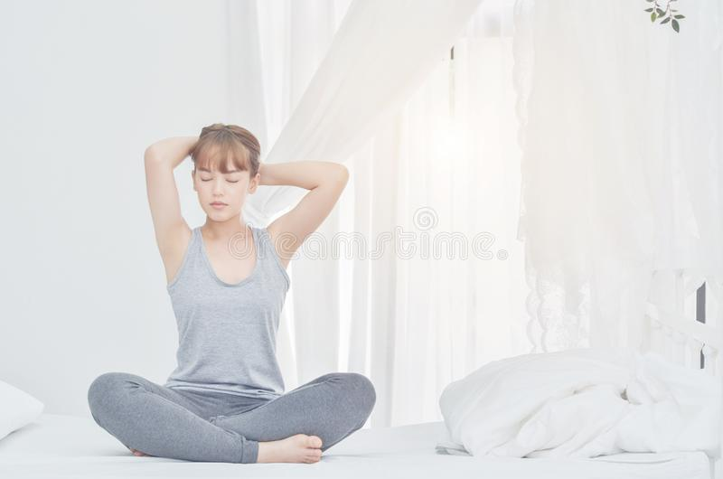 Women wearing gray pajamas sitting on the couch Use the handle to the foot. stock photo