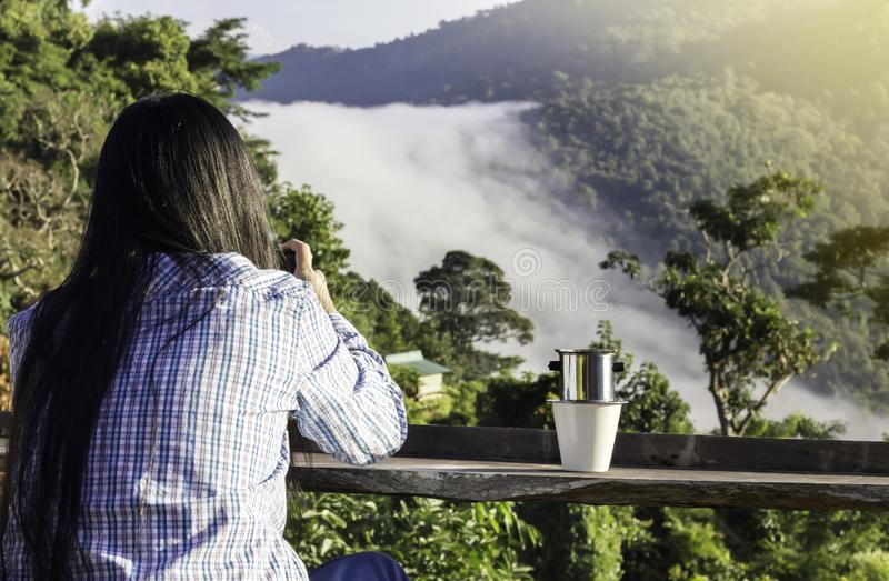 Women sit and looking fog on the cliff, forest and mountain nature view royalty free stock photography