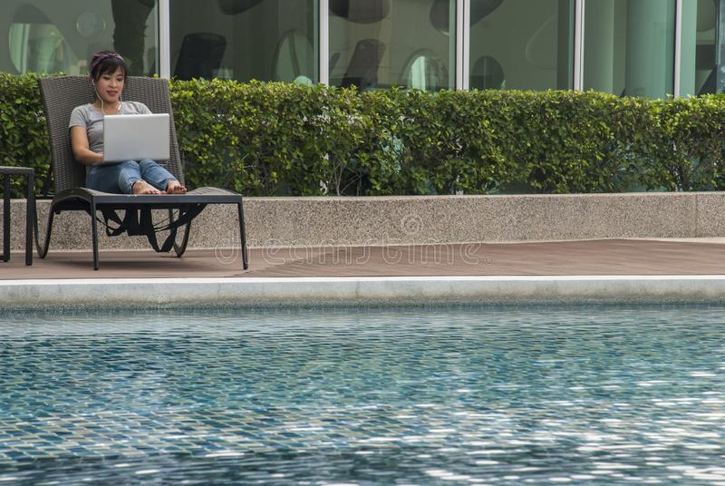 Women sitting on a laptop by the pool royalty free stock photos