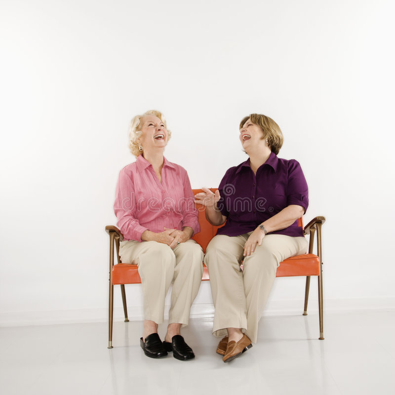 Women sitting laughing. stock photography