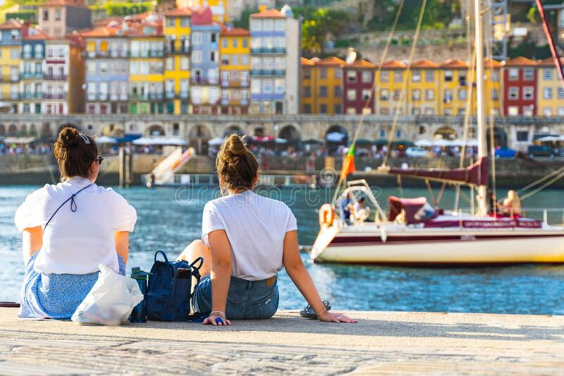 Women sitting on a pier in a harbor and enjoying view of Porto, Portugal. back view girls. Panoramic old city Porto at river Duoro. Oporto panorama. wallpaper stock image