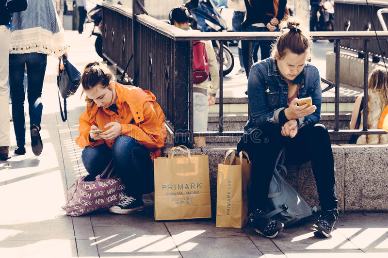 Women sitting on the street with shopping bags texting on thier stock photography