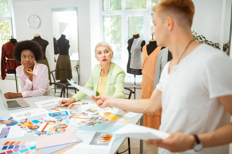 Women sitting at the table in a studio. At the table. Two women sitting at a cutting table in a fashion designers studio while listening to their colleague stock image