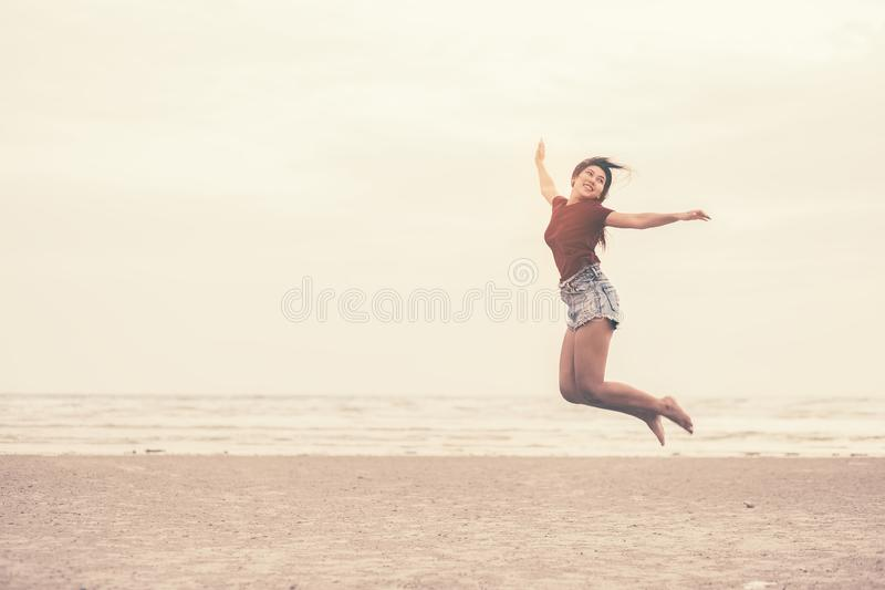 A women smile and jump on the beach stock photo
