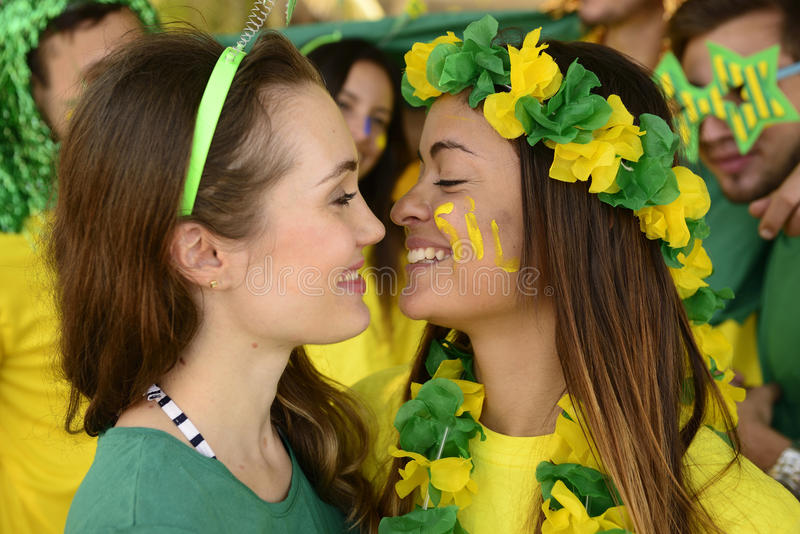 Women soccer fans almost kissing each other. royalty free stock photography
