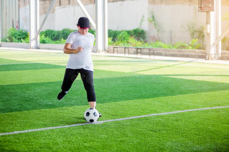Women soccer player put black sport shoes and run for shoot ball to goal on artificial turf stock images