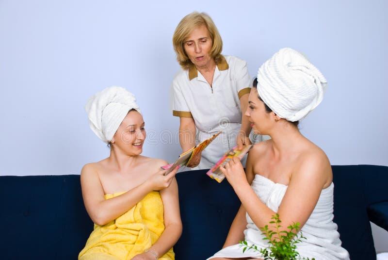 Women at spa receiving magazines royalty free stock photos
