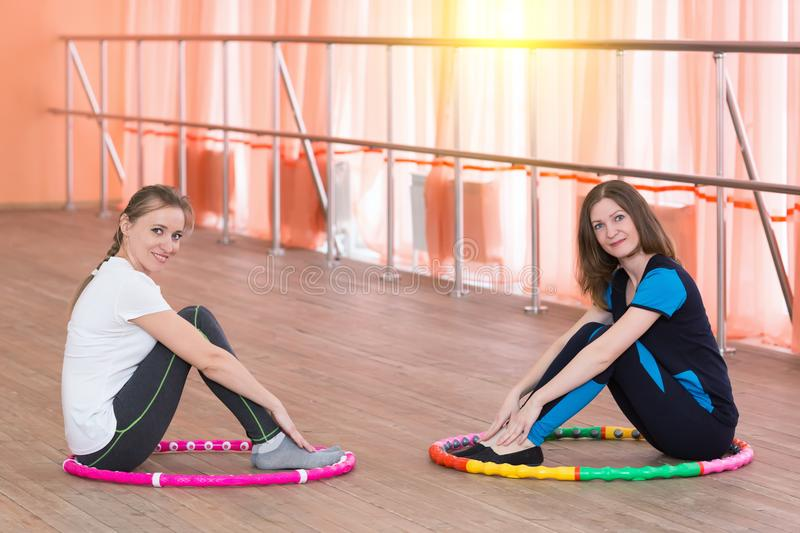 Two young girls in the gym are sitting on the floor. stock photos