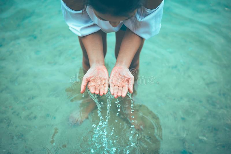 A women stand in the water and hands fetch water and have water splash stock photography