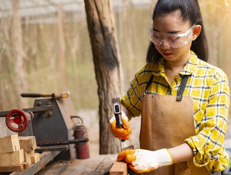 Women standing builder wearing checked shirt worker of construction site hammering nail in the wooden stock photo