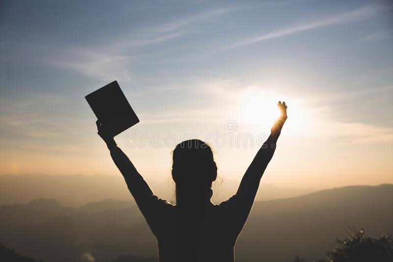 Women standing holding holy  bible for worshipping God at sunset background, Pray to the god, christian silhouette concept stock photos