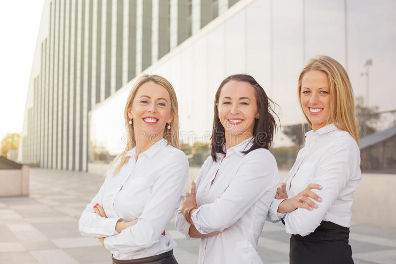 Women standing and smiling with their hands crossed. Three women standing and smiling with their hands crossed royalty free stock photography