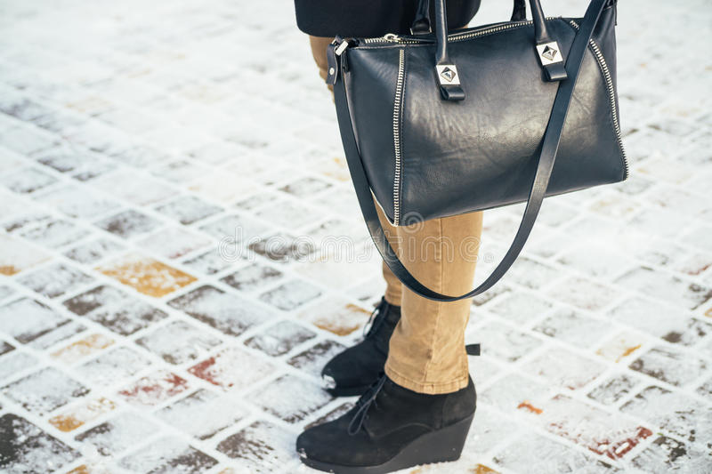 Women standing on a snow-covered sidewalk with handbags, close-up royalty free stock photos