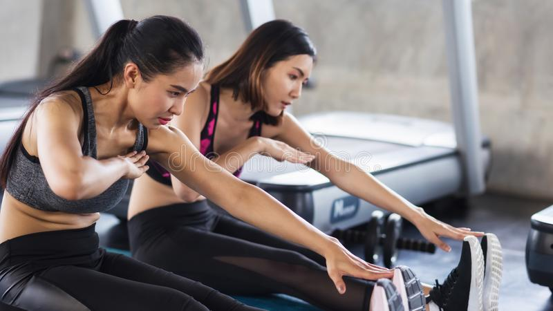 Women stretch hands to legs in gym. Two Asian young women stretch hands to legs together in fitness gym. Each of them reach foot with one hand. Bodybuilding royalty free stock photos