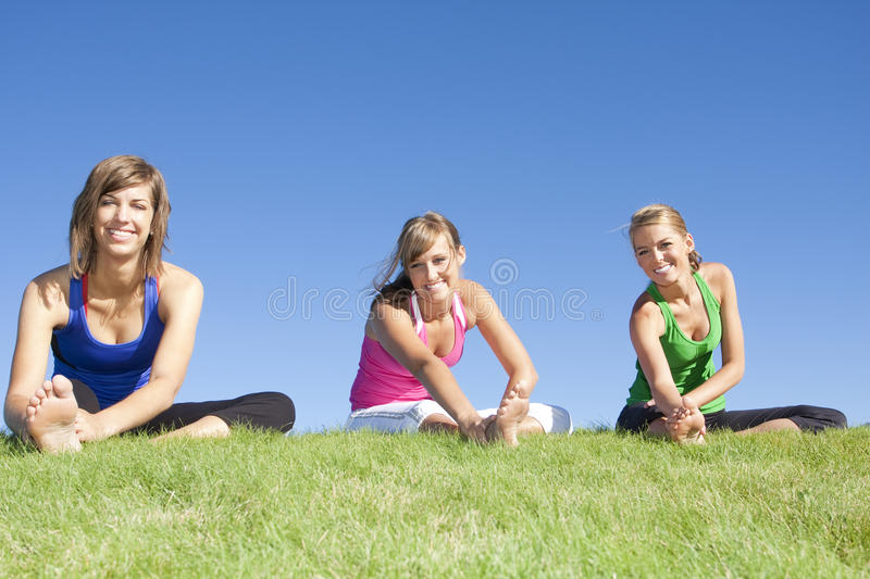 Women stretching before exercise. A group of Beautiful young women stretching before fitness and yoga outdoors royalty free stock image