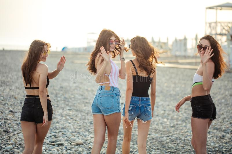 Women strolling along coastline. female friends walking together on beach, enjoying summer vacation stock image