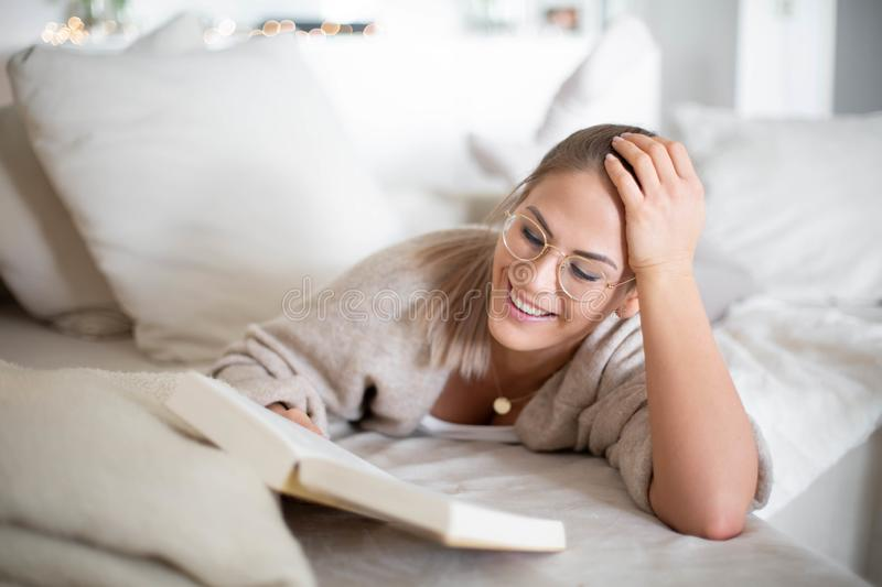 Women is studying, lying on the sofa in living room at home stock images