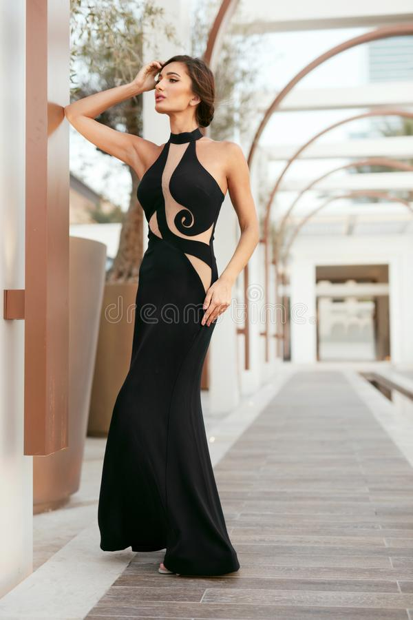 Women Style. Fashion Girl In Long Black Dress Posing Outdoors stock photography