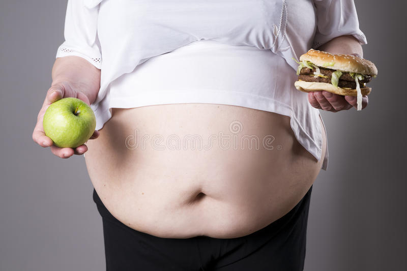 Women suffer from obesity with big hamburger and apple in hands. Junk food concept royalty free stock photos