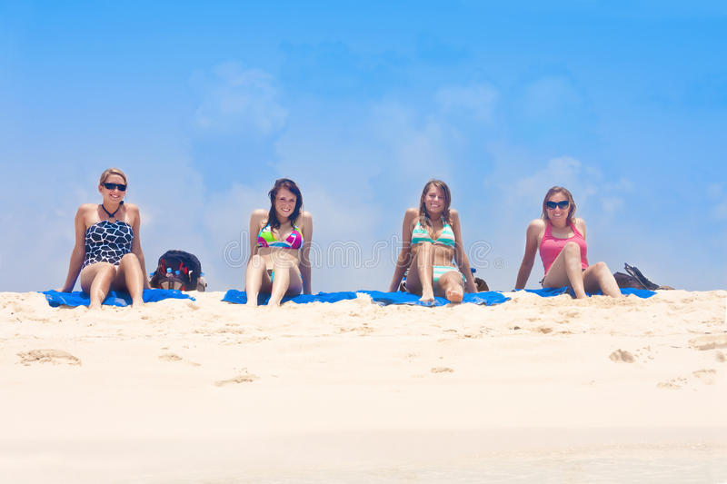 Women Sunbathing on the beach. A group of young adults sitting on the beach enjoying the view of the Caribbean Ocean royalty free stock photos