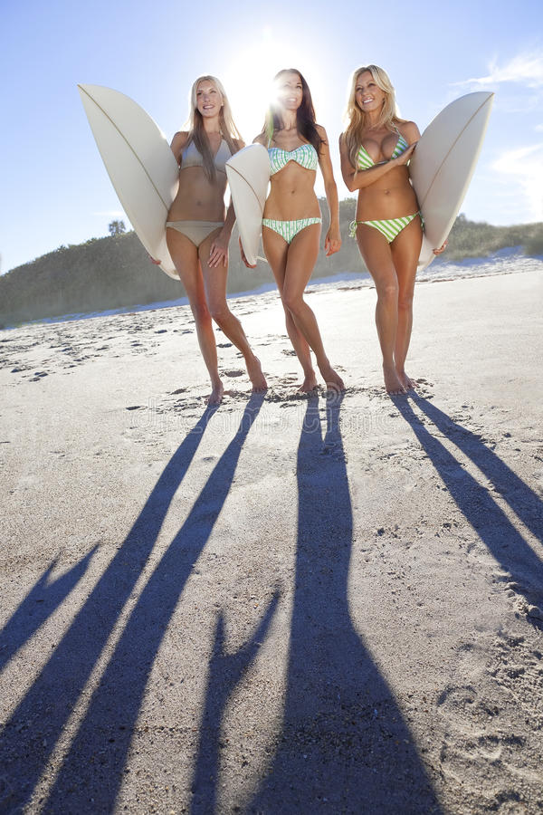 Women Surfers In Bikinis With Surfboards At Beac stock image