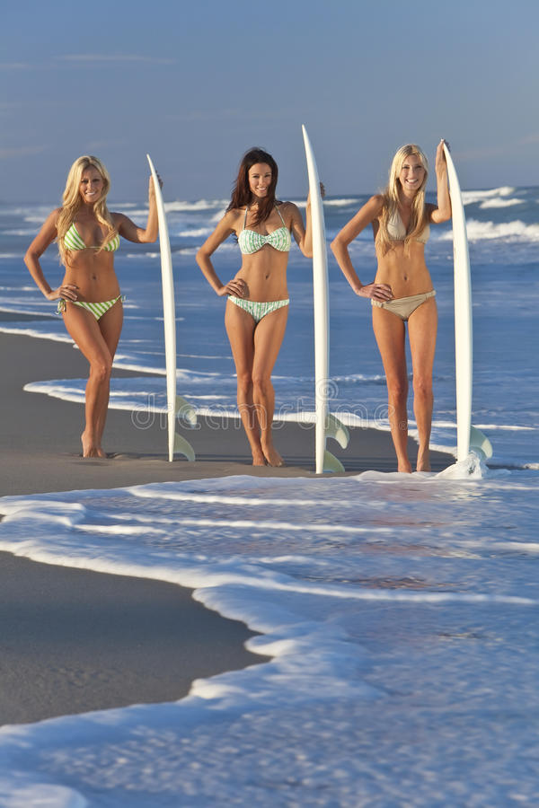 Women Surfers On Bikinis With Surfboards At Beac royalty free stock photography