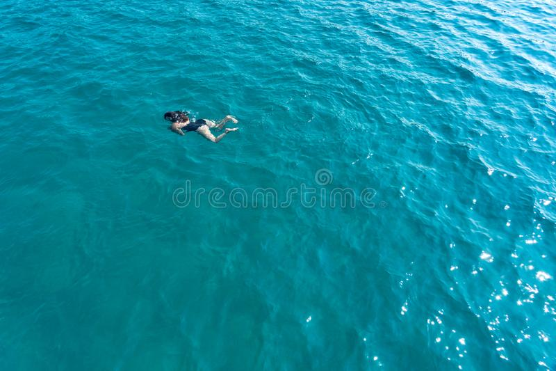 Women swimming alone under water in the sea view from above.  stock photo