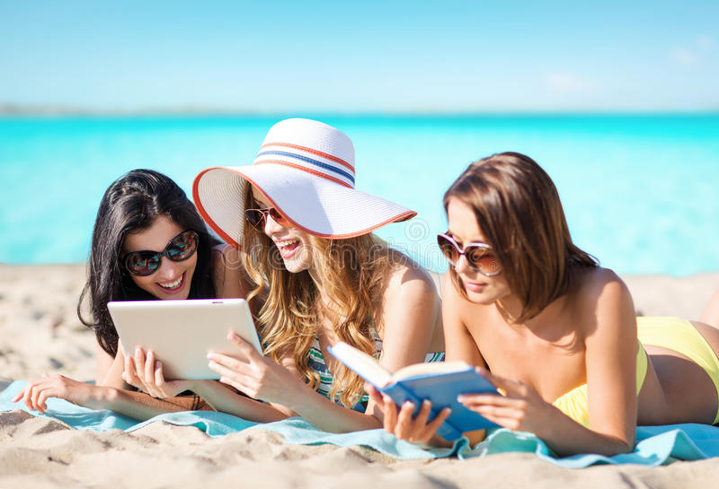 Women with tablet pc and book on summer beach. Summer holidays, technology, people, travel and internet concept - happy young women in bikinis with tablet pc stock images