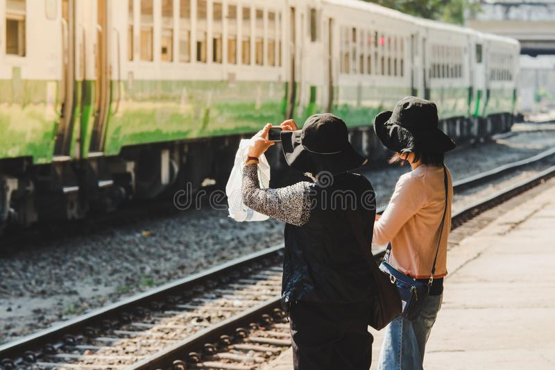 Women take photo of old trains in the train station. Yangon, Myanmar royalty free stock photos