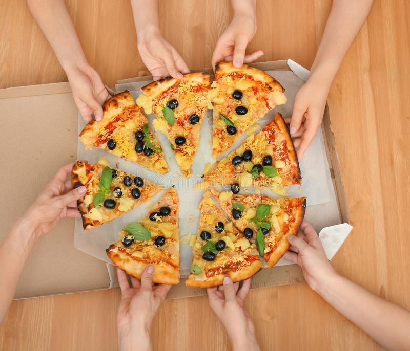 Women taking slices of tasty Italian pizza from box on wooden table, top view royalty free stock photo