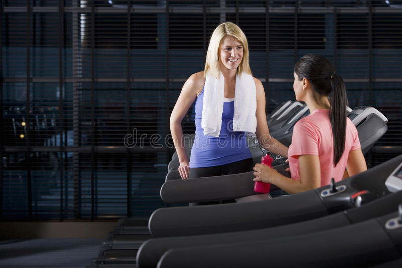 Women talking face to face on treadmills at health club royalty free stock images