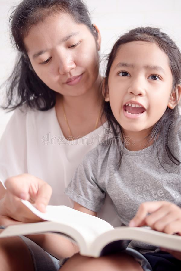Women teaching girl to reading a book stock photo