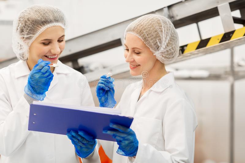 Women technologists tasting ice cream at factory stock image