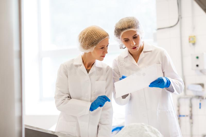 Women technologists working at ice cream factory stock photo