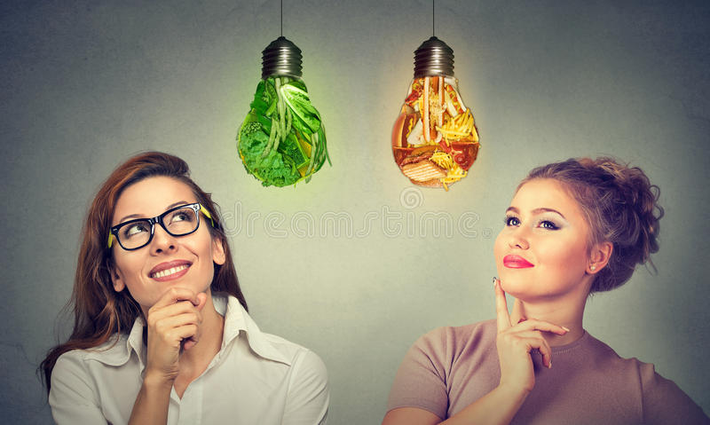 Women thinking about diet looking at vegetables junk food lightbulb stock photos