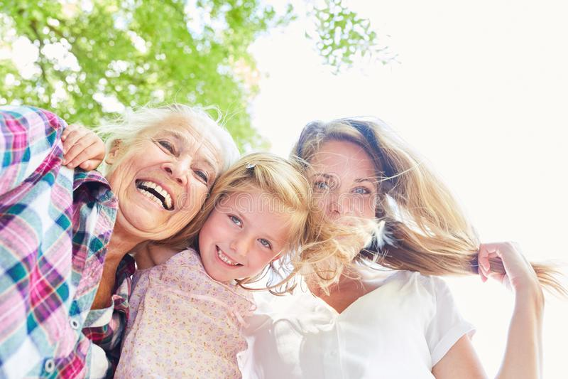 Women in three generations with grandma and granddaughter. Happy women in three generations with grandma and granddaughter together in the sunshine stock image