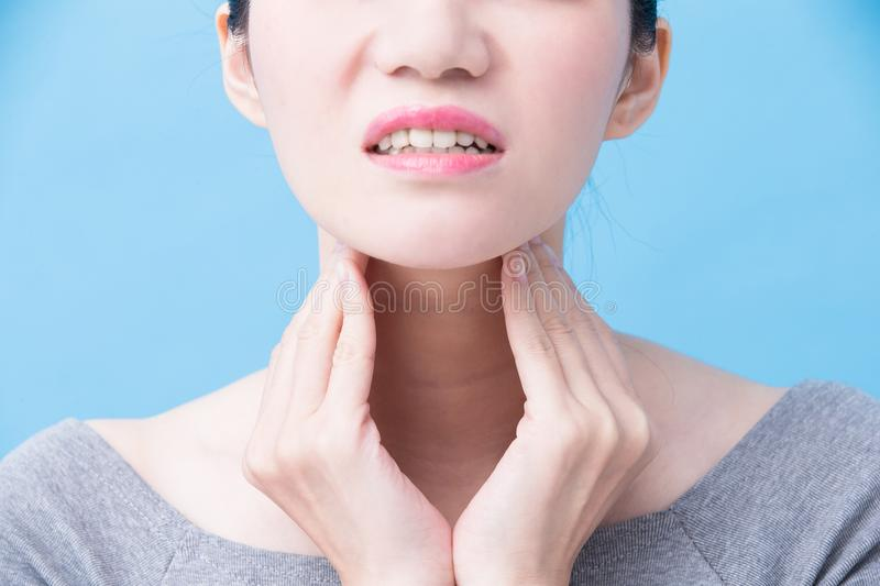 Women with thyroid gland problem. On the blue background royalty free stock photo
