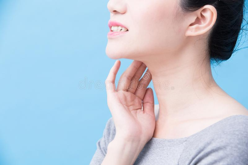 Women with thyroid gland problem. On the blue background stock photography