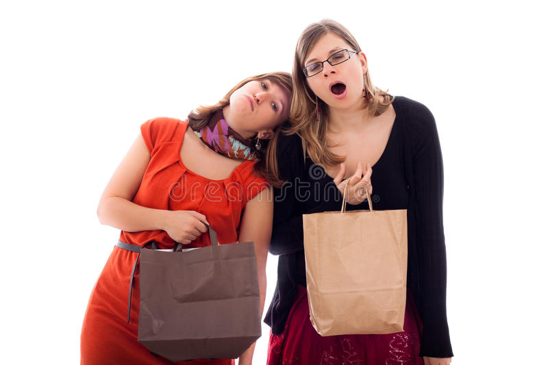 Women tired of shopping. Two young women tired of shopping, isolated on white background royalty free stock photos