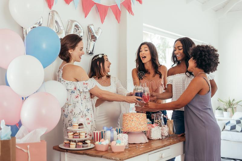 Women toasting with juices at baby shower party. Group of friends at baby shower party having juices royalty free stock images