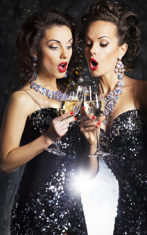 Women toasting at party with wineglasses. Couple of cheerful women toasting at party with wine glasses - celebration royalty free stock photo