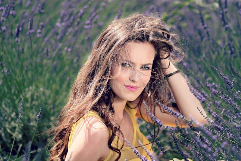 Women' top sin mangas del amarillo de s que se sostiene el pelo rizado de Brown mientras que se sienta en una flor púrpura fotos de archivo libres de regalías
