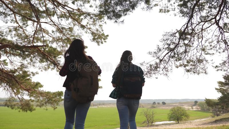 Women tourists go through forest. Sexy female travelers with backpacks straighten their arms to side, enjoying freedom royalty free stock images