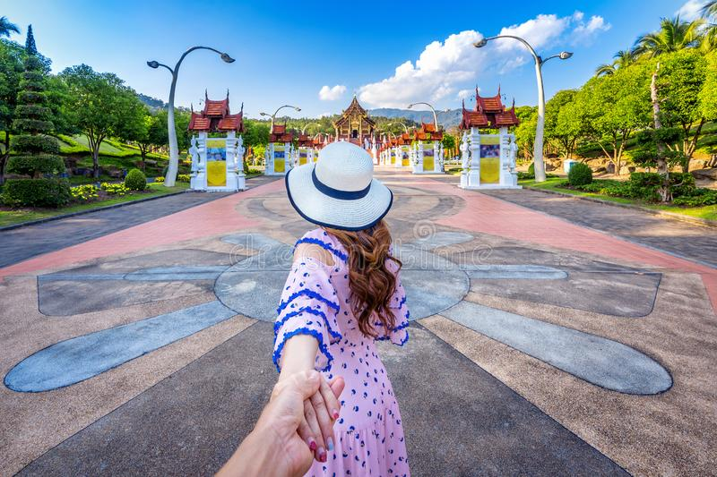 Women tourists holding man`s hand and leading him to Ho kham luang northern thai style in Royal Flora ratchaphruek in Chiang Mai,T. Hailand stock photography