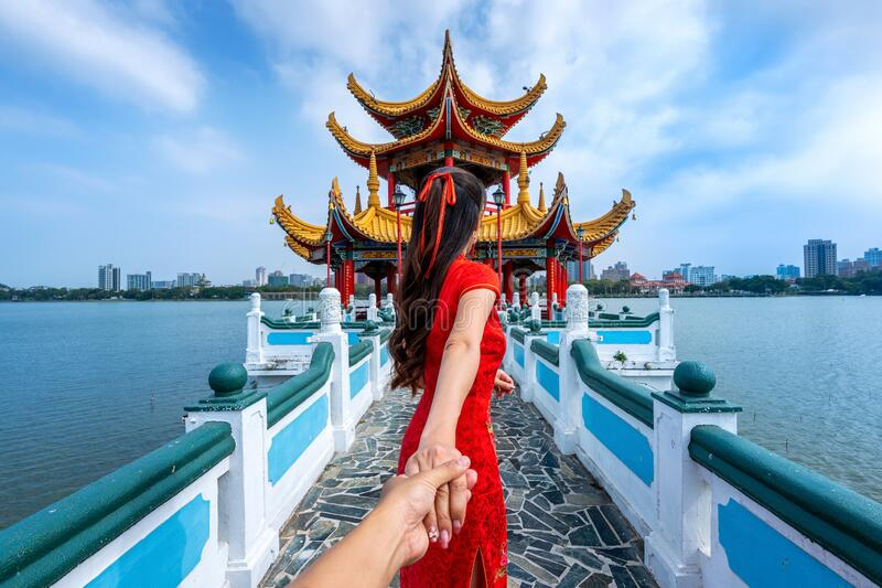 Women tourists holding man`s hand and leading him to Kaohsiung`s famous tourist attractions in Taiwan.  royalty free stock photography