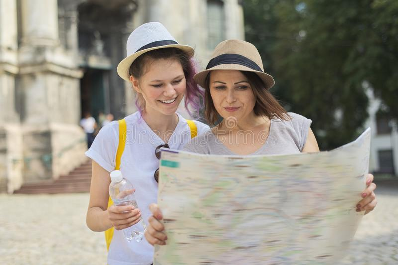 Women tourists mother and daughter teenager with map stock photography